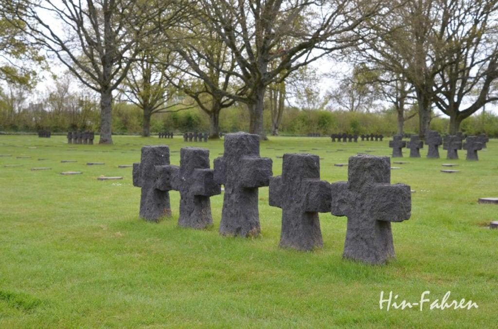In kleinen Gruppen stehen Kreuzreihen auf dem Kriegsgräberfeld
