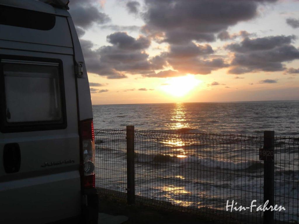 Normandie mit Wohnmobil: Die Sonne spiegelt sich auf dem Meer vor dem Kastenwagen