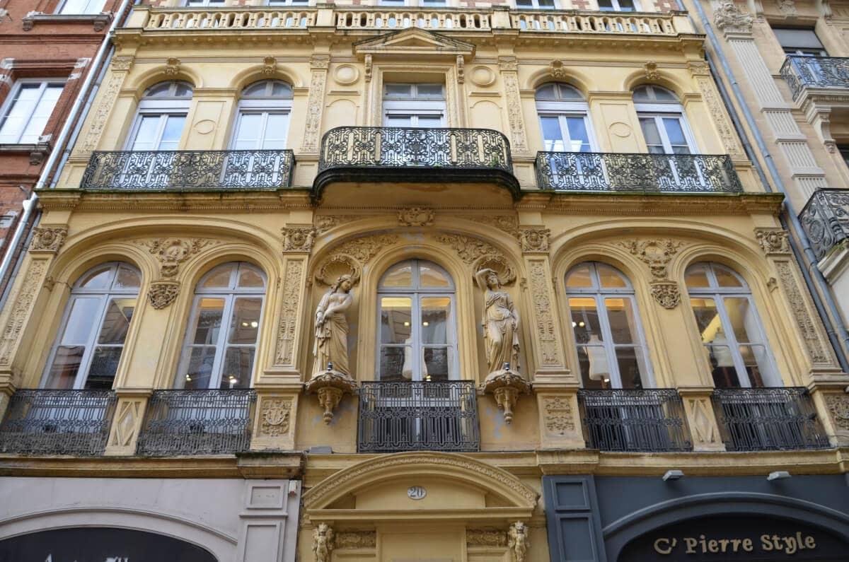 Stadthaus mit Skulpturen und geschmiedeten Balkongittern