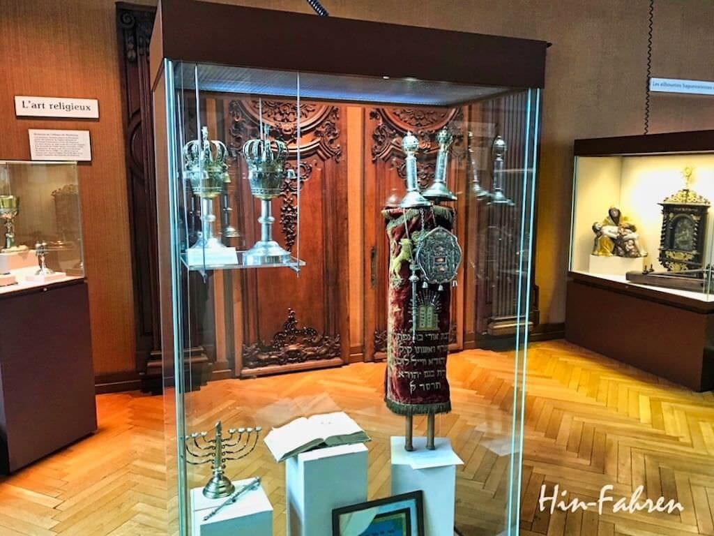 Torahrolle, siebenarmiger Leuchter und im Hintergrund Meßkelch und Pieta im Museum Haguenau