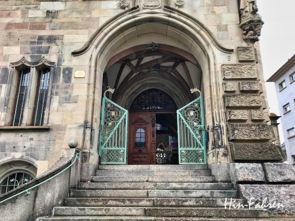 Ideales Ziel für einen Ausflug: Ein Gebäude fast wie ein Schloss mit Treppe, Gitter und großer Holztür