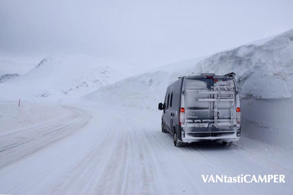 Schnee auf der Straße, hohe Schneeberge neben der Straße, vereister Pössl-Kastenwagen im Winter