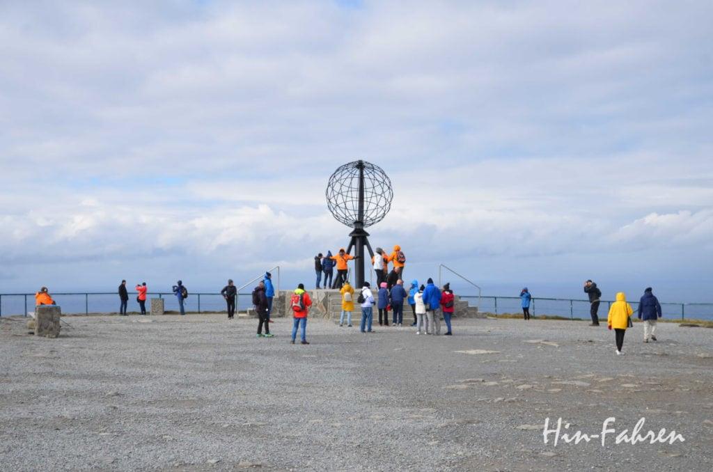 Eine Reisegruppe in bunten Jacken rund um den Globus am Nordkap