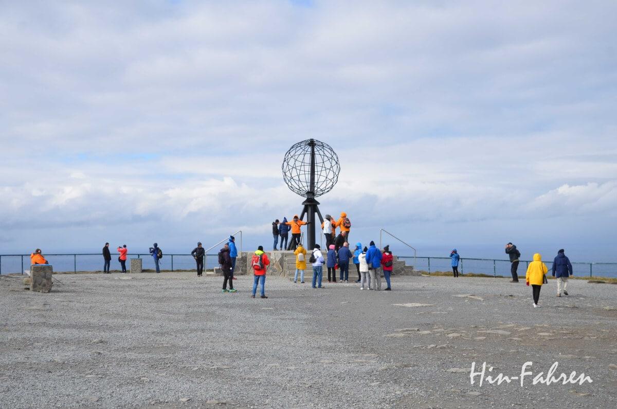 Eine Reisegruppe in bunten Jacken rund um den Globus