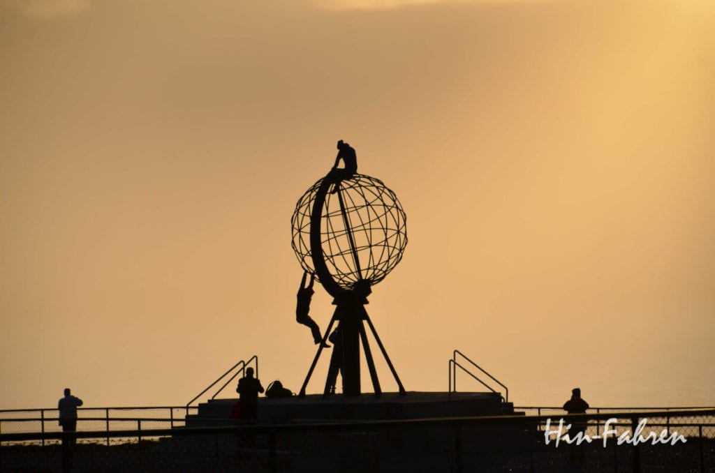 Globus und Besucher am Nordkap als Schattenriss in der Mitternachtssonne