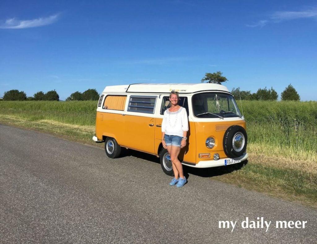 Gelber Campingbulli Westfalia VW T2 von 1972 und die stolze Besitzerin