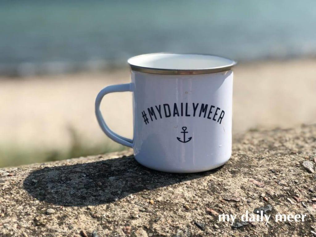 Tasse für das Wohnmobil auf einer Mauer am Meer