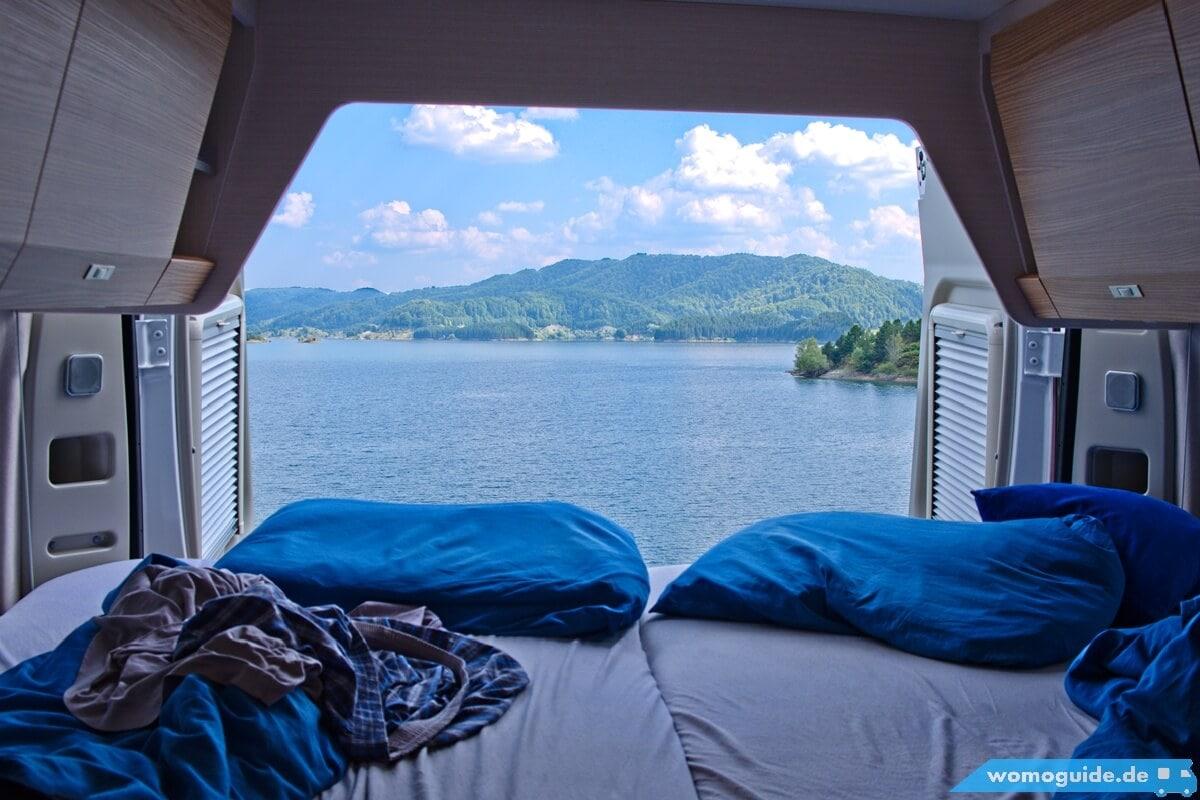 Blick aus den Hecktüren des Kastenwagen direkt auf einen schönen See