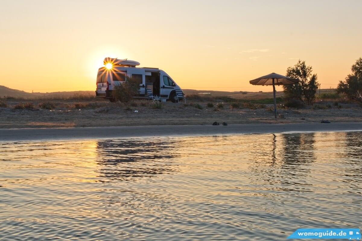 Kastenwagen bei Sonnenuntergang am Strand