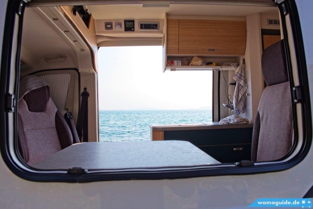 Blick durch den Kastenwagen auf das Meer dahinter