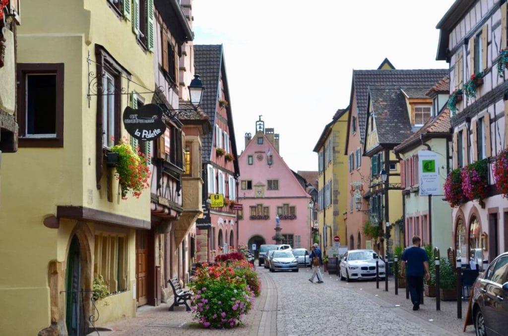 Grand Rue in Turckheim mit Fußgängern, Autos und historischen Häusern