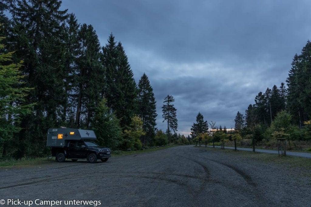 Pickup mit Wohnkabine auf einem Parkplatz im Wald