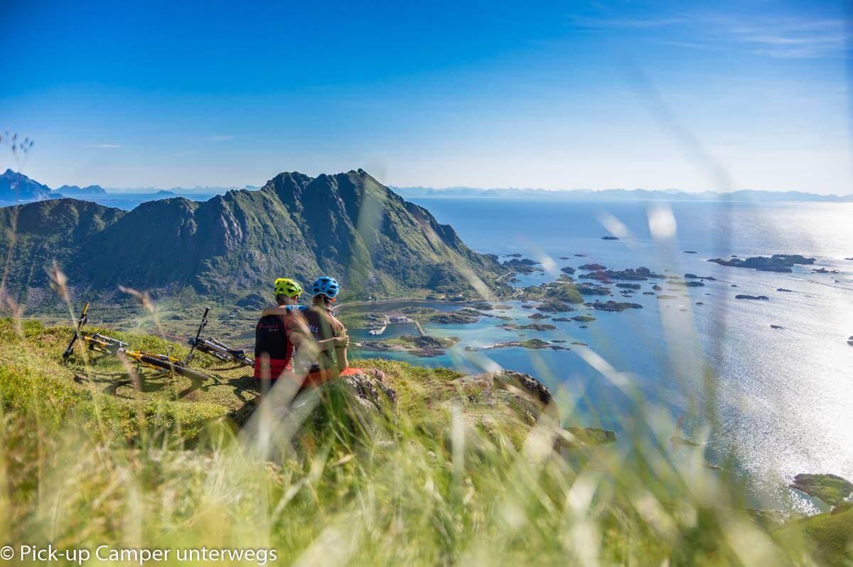 Paar sitzt auf dem Gipfel und blickt aufs Meer, man sieht kleine Inseln und das Gebirge in der Ferne