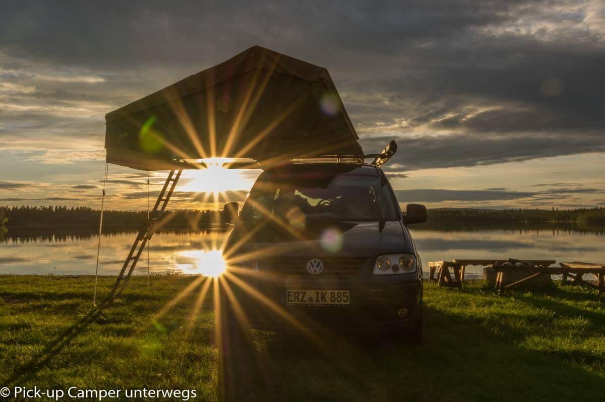 PKW mit Dachzelt am See in Skandinavien