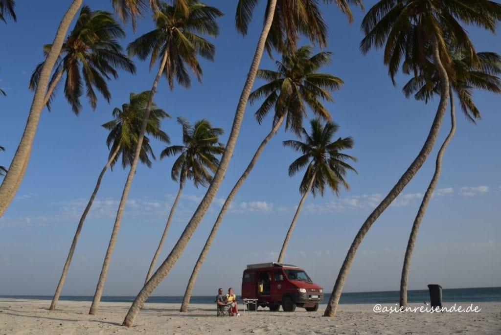 Kastenwagen am Strand unter Palmen im Oman