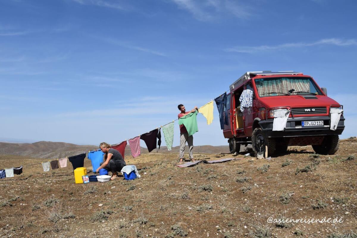 Kastenwagen mit Wäscheleine und Wäsche in der Wüste