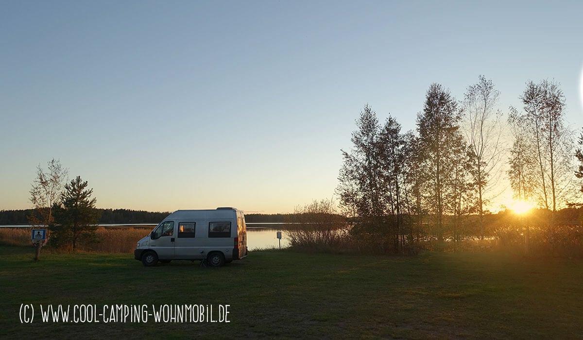 Kastenwagen am See beim Sonnenuntergang