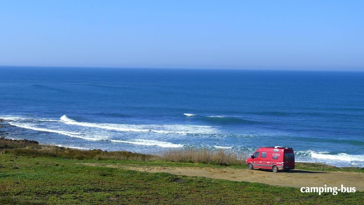 Roter Kastenwagen steht mit Blick aufs Meer
