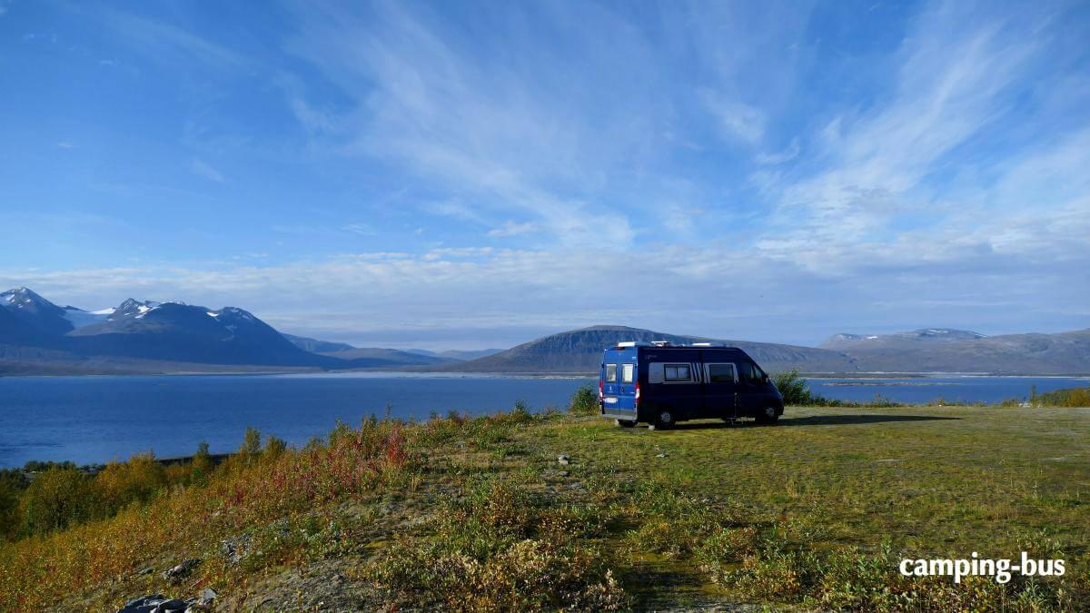 Blauer Kastenwagen zwischen Gebirge und Fjord