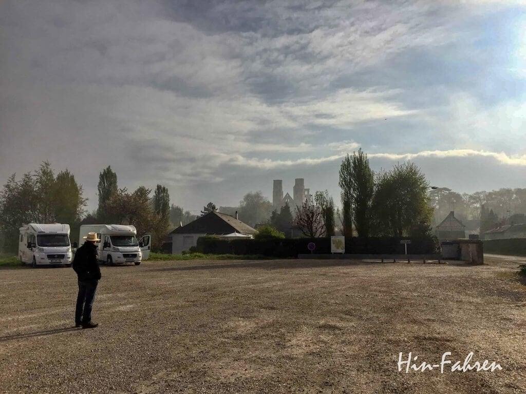 Wohnmobile auf dem Wohnmobilstellplatz und Türme der Ruine Jumieges in der Normandie