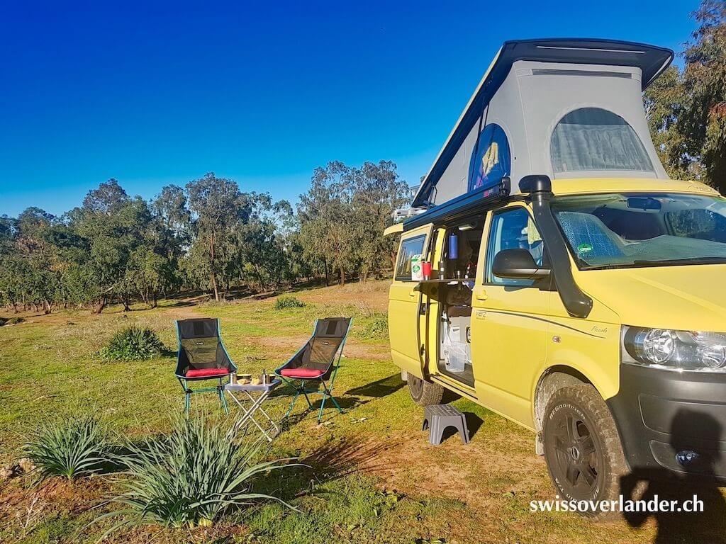 VW Bus mit hochgeklapptem Dach und Campingstühlen