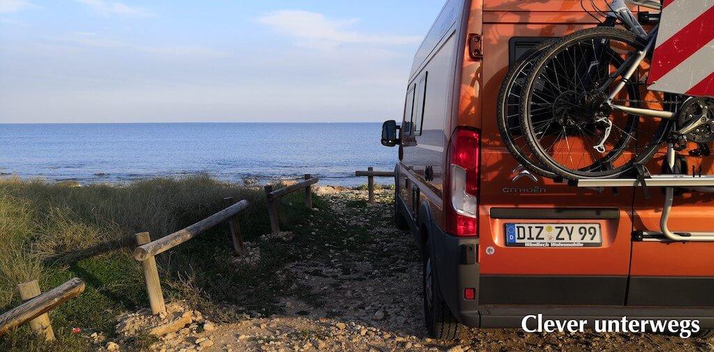 Oranger Kastenwagen von Clever und Blick aufs Meer