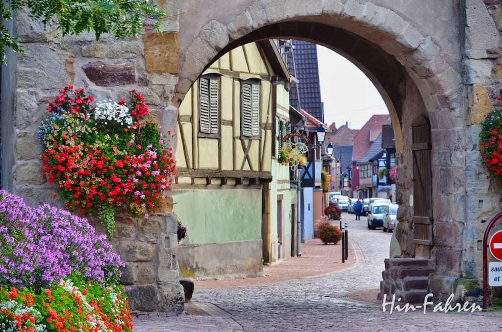 Stadttor, Blumen und Fachwerkhäuser