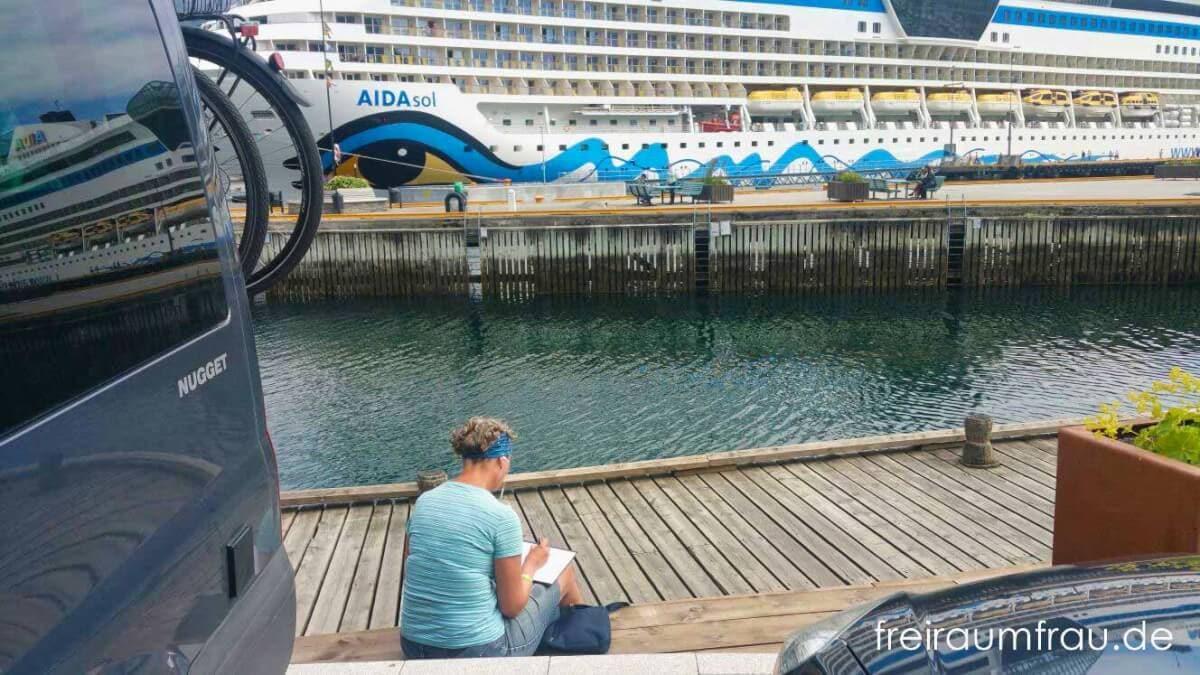 Ford Nugget Wohnmobil am Wasser vor einem Kreuzfahrtschiff