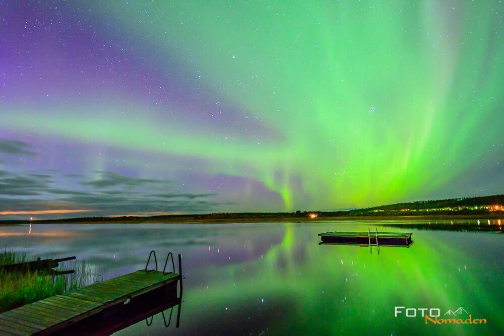 Grüne und blaue Nordlichter über dem Wasser