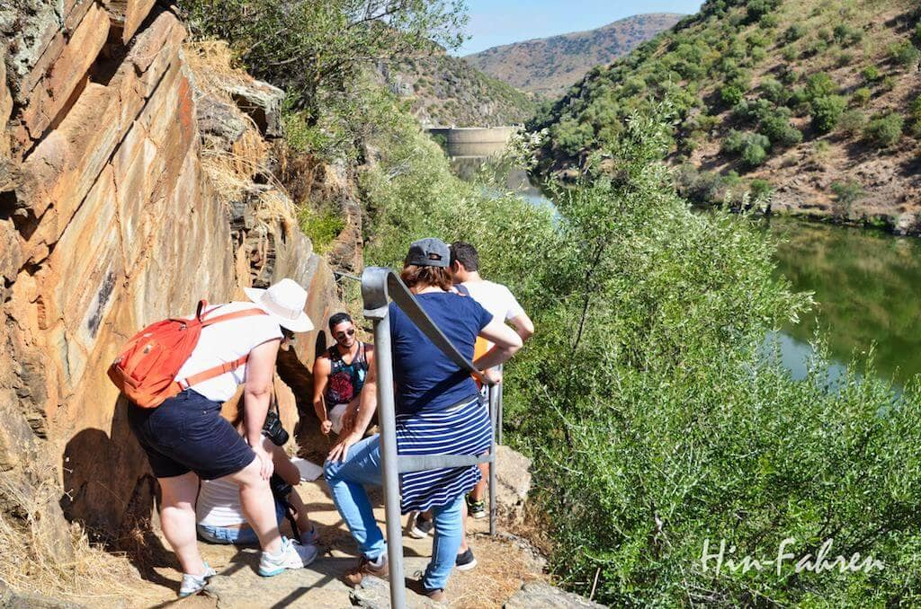 Eine Gruppe schaut sich Felsbilder an