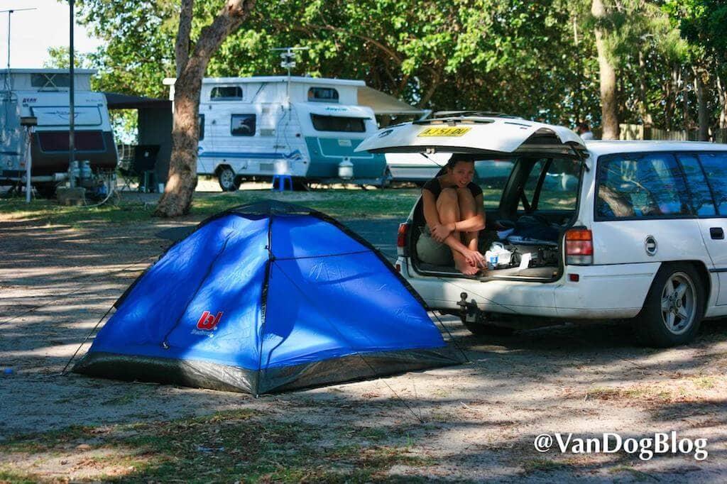 Junge Frau sitzt im Auto, daneben ein Zelt