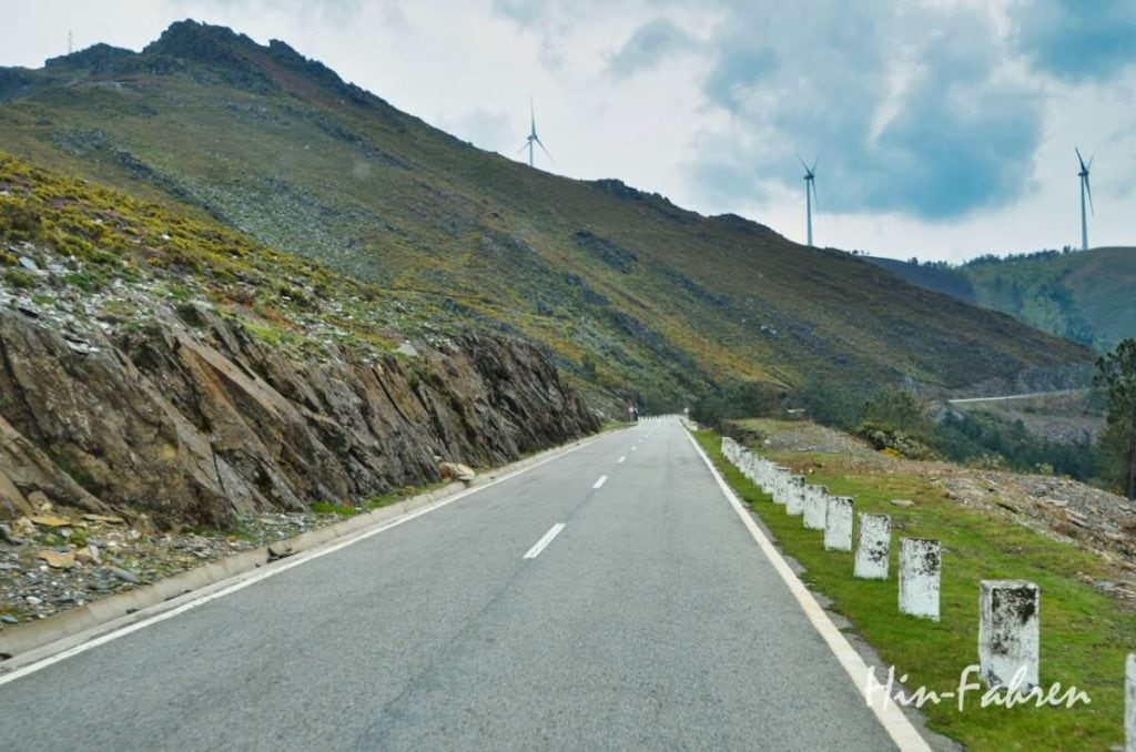 Straße durch karge Berge in Nord-Portugal, auf dem Bergkamm stehen Windräder