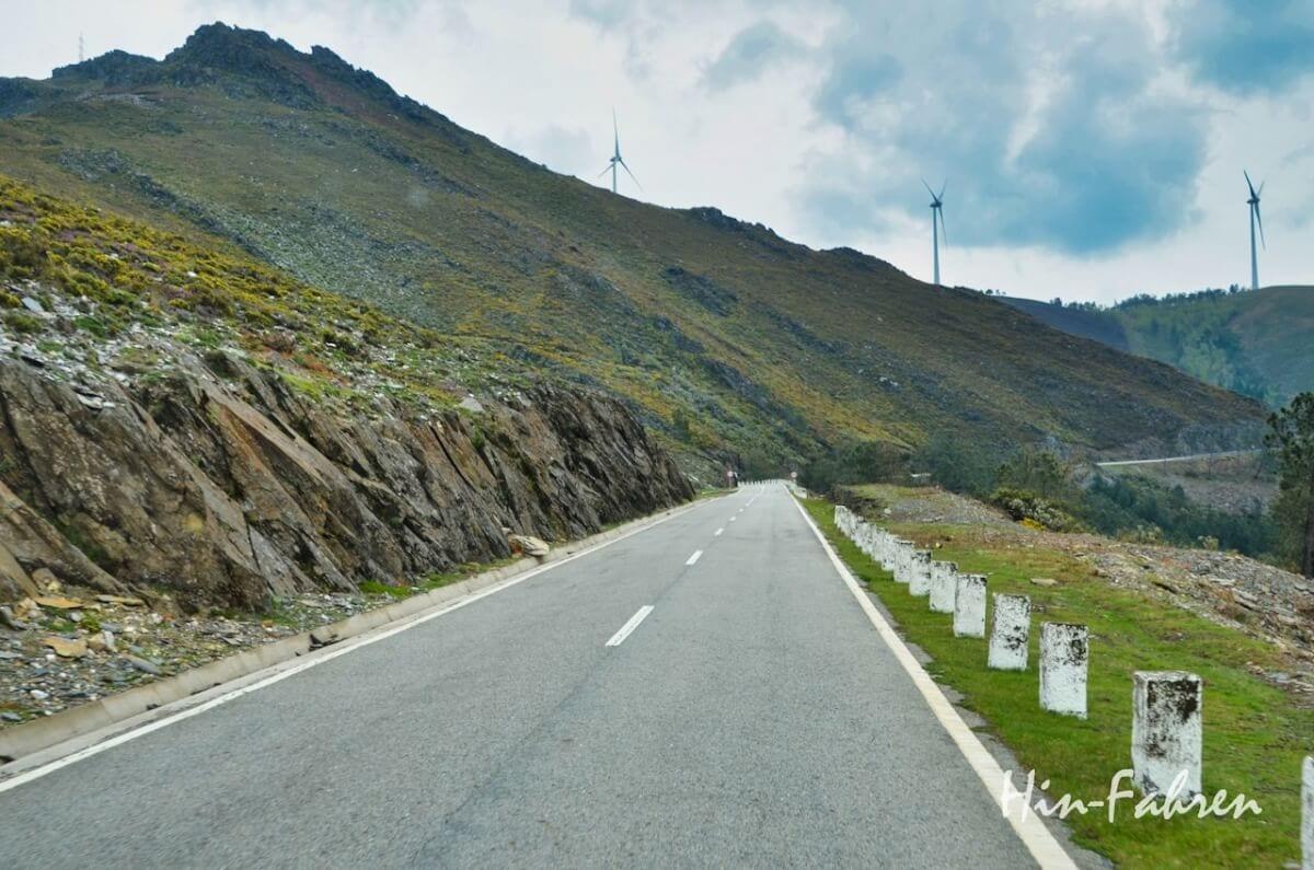 Straße durch karge Berge in Portugal, auf dem Bergkamm stehen Windräder
