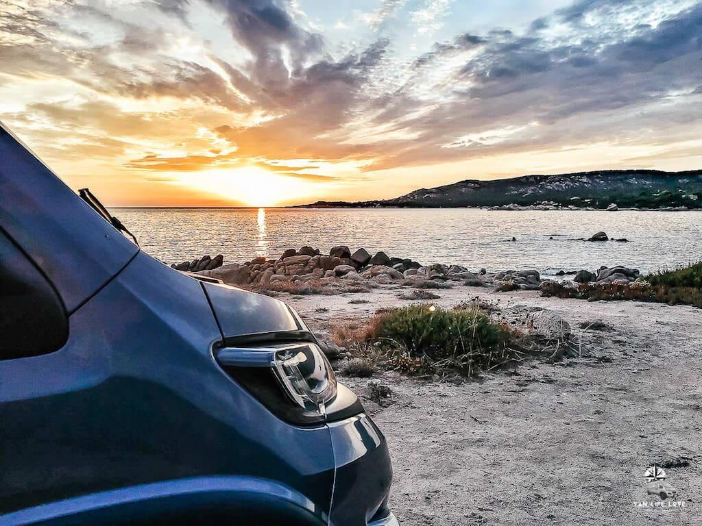 Kastenwagen steht bei Sonnenuntergang am Meer