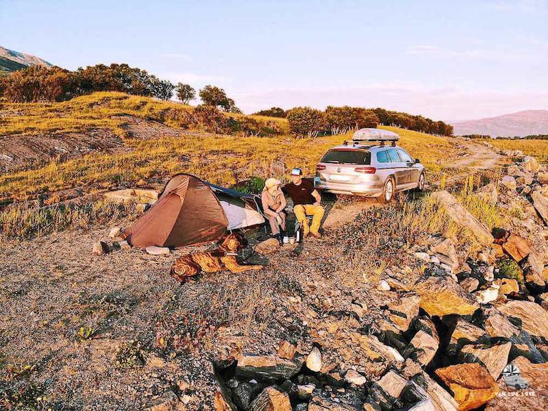 Zelt, Hund, Paar, Auto in schöner Landschaft beim Camping