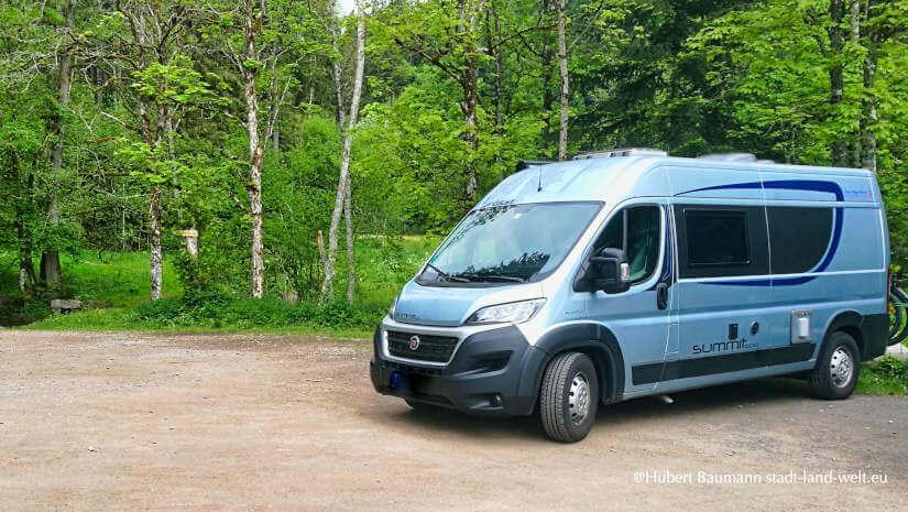 Camper unterwegs: Kastenwagen Pössl Summit auf einem Parkplatz im Wald