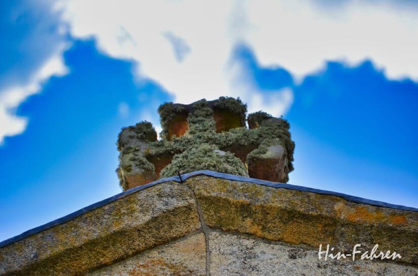 Wohnmobil-Reise: Mit Moos bewachsenes Kreuz auf einer alten Kirche